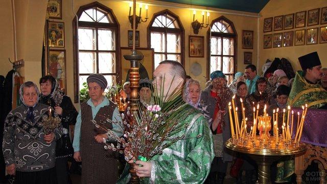 Прихожанки церкви и священник с вербой в руках