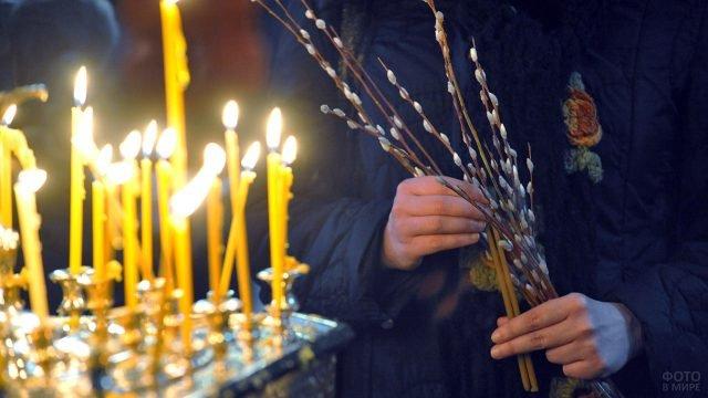 Верба в руках прихожанки церкви, стоящей перед свечами