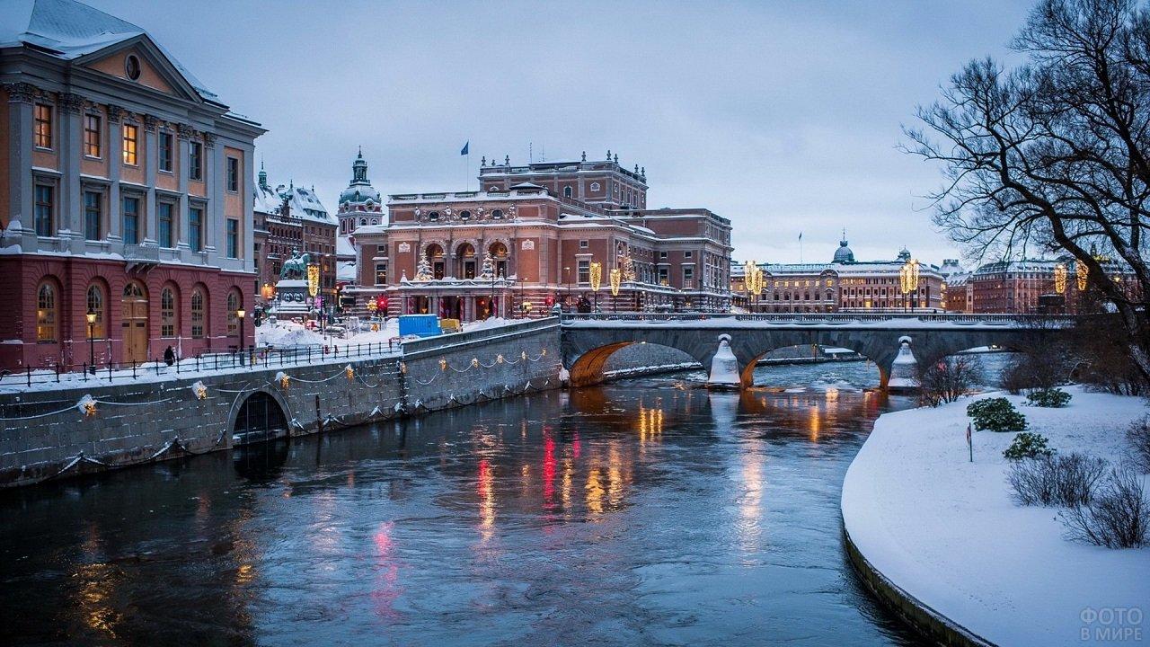 Берега Москвы-реки, покрытые снегом в освещении новогодних украшений города