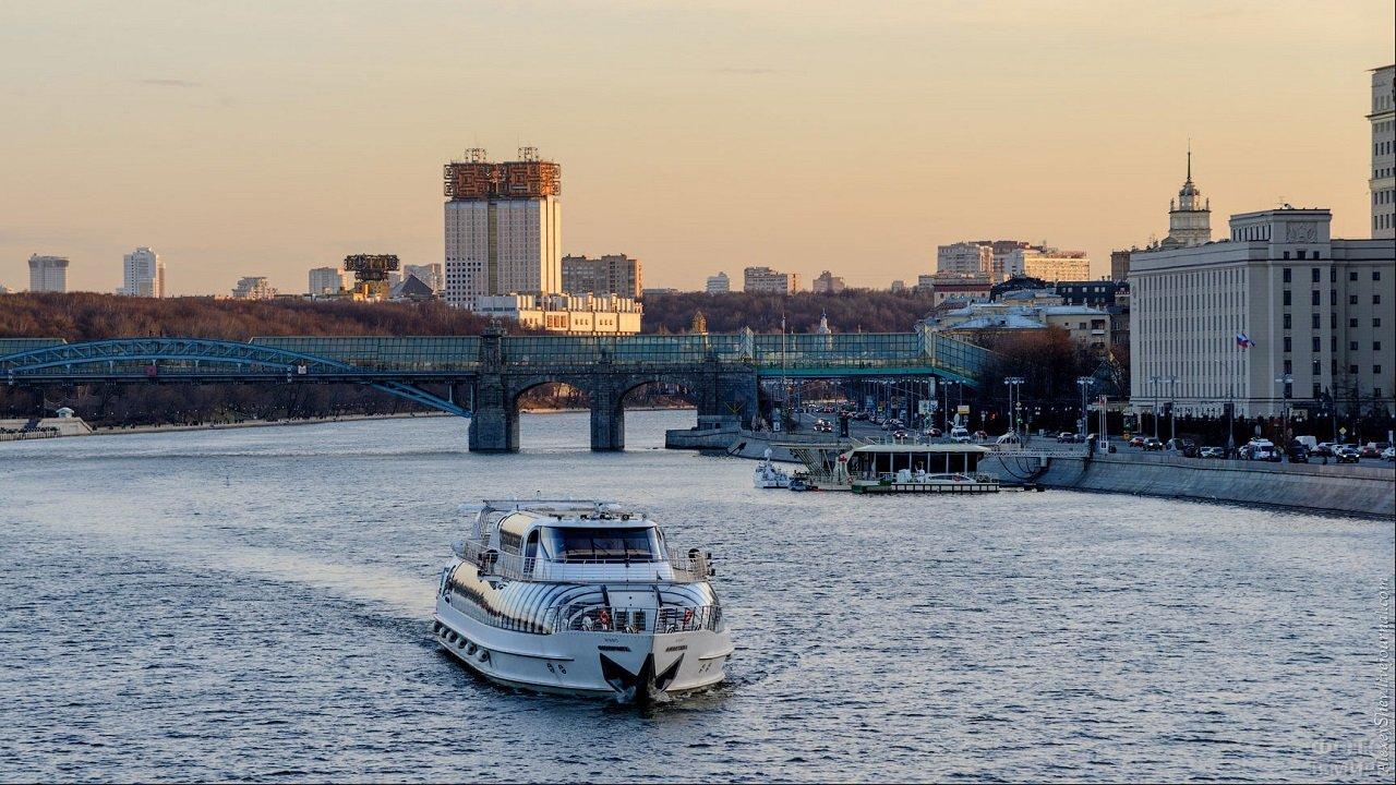 Лайнер плывущий по реке на фоне городских зданий