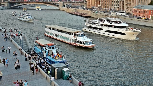 Люди гуляют по набережной вдоль реки, по которой проплывают корабли