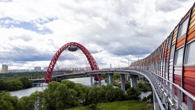 Мост в ярких красках с необычной аркой с видом на реку