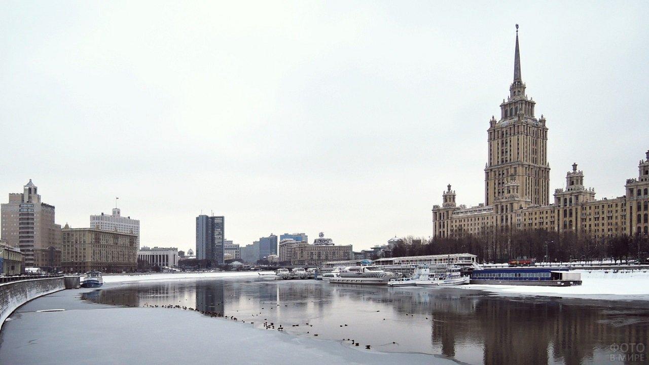 Наполовину замёрзшая река с видом на городские постройки