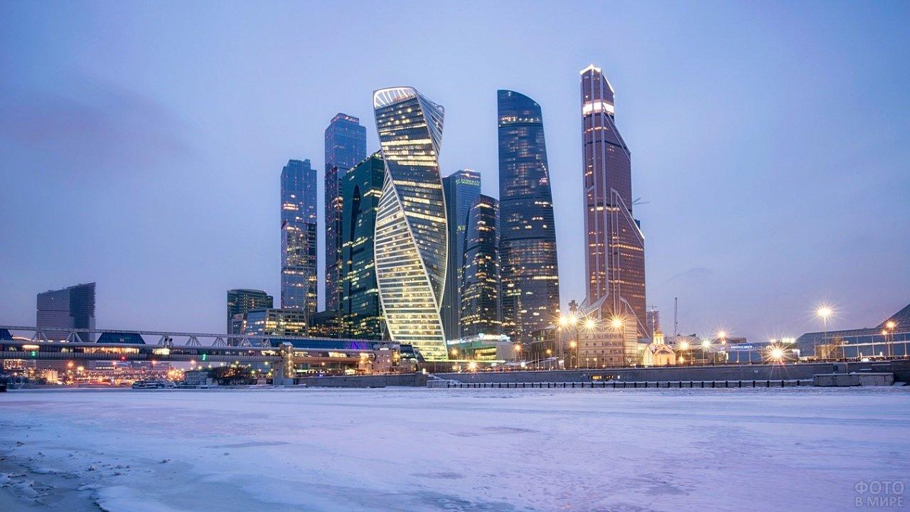 Покрытая льдом река на фоне ярко освещённых небоскрёбов