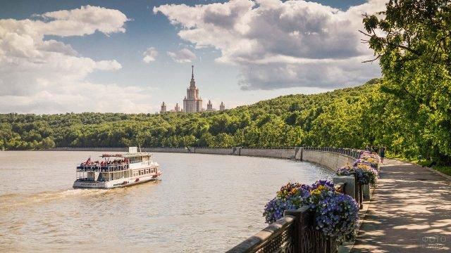 Теплоход, возящий людей по реке вдоль живописного парка