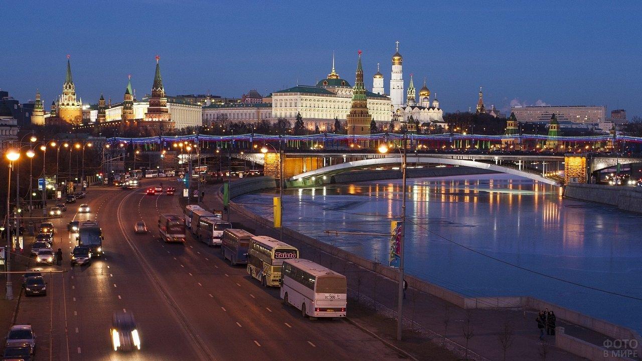 Вечерняя оживлёная трасса Москвы на фоне спокойной реки