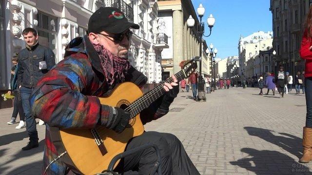 Мужчина в кепке, солнечных очках и шарфе играет на гитаре