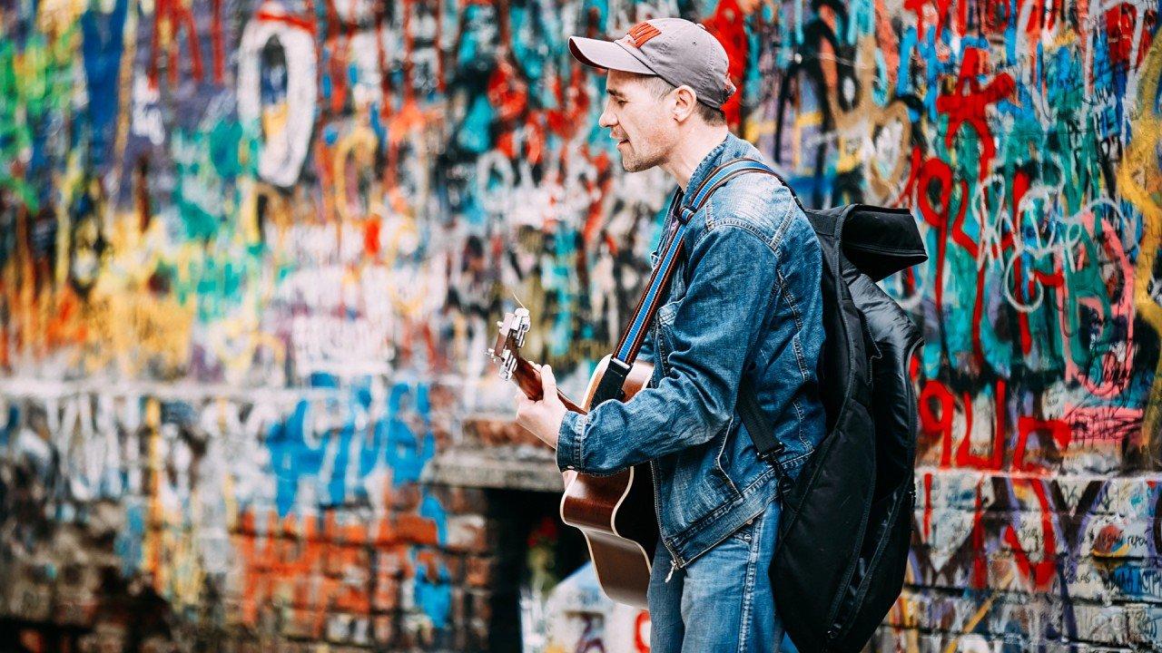Парень с гитарой поёт песни у стены памяти Виктора Цоя