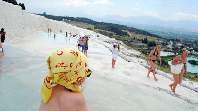 Девочка наблюдает за туристами на одном из уровней террасных ванн в Памуккале