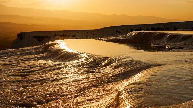 Отблески заката на глянцевой поверхности каскада в Памуккале