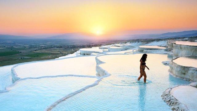Туристка в купальнике в террасных ваннах Памуккале на закате дня