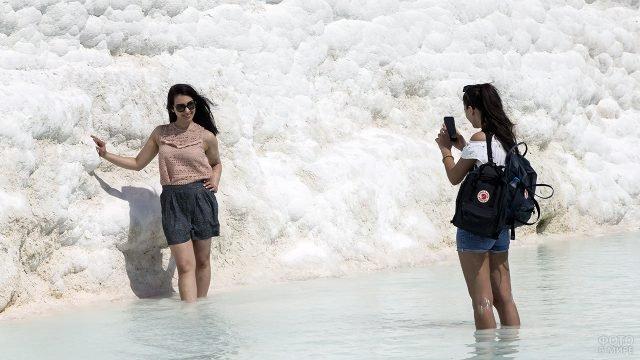 Туристки фотографируются в одной из травертин в Памуккале