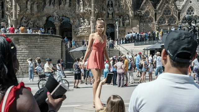 Красивая туристка фотографируется на фоне Саграды Фамилии