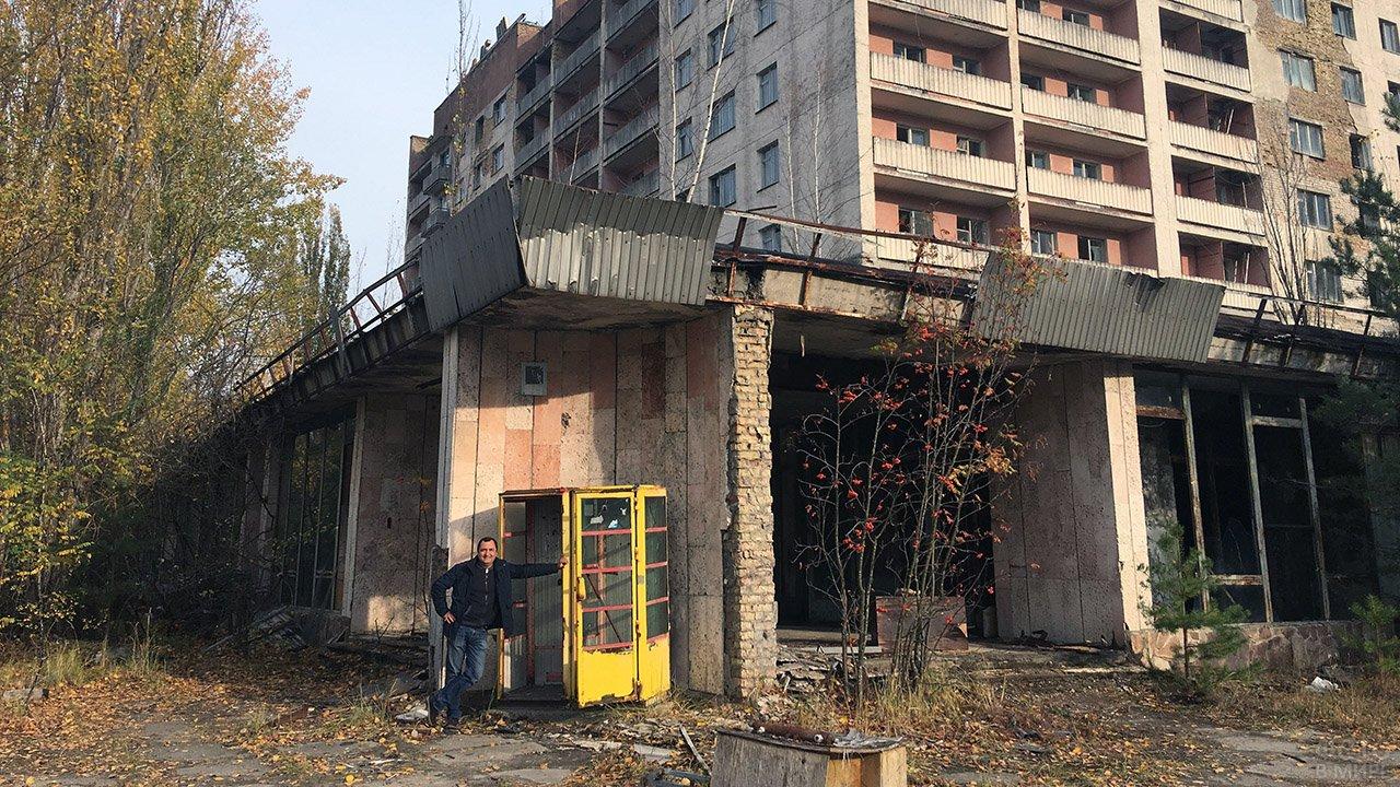 Индустриальный турист у бывшей телефонной будки в заброшенном городе Припять
