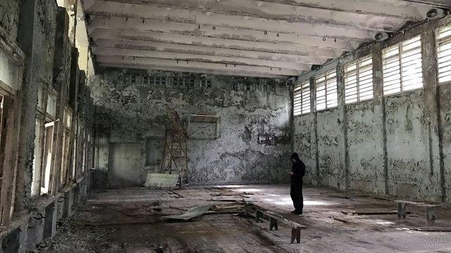 Индустриальный турист в заброшенном спортзале школы в Припяти