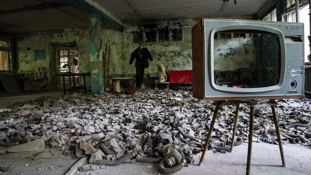 Постановочное фото с противогазами на полу заброшенного здания в городе-призраке Припять