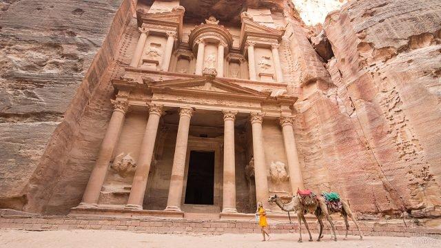 Девушка в жёлтом платье с верблюдами на фоне входа в храм