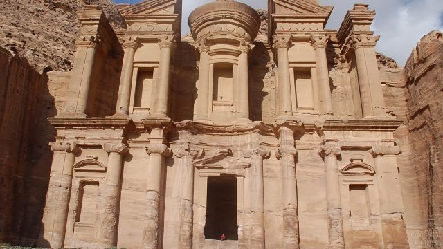 Турист сидит на входе в древний храм