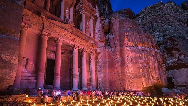 Туристы сидят на ступенях храма среди свечей вечером