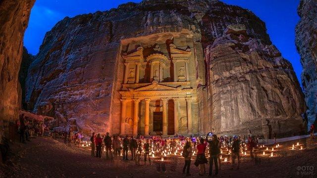 Туристы ставят свечи к храму вечером