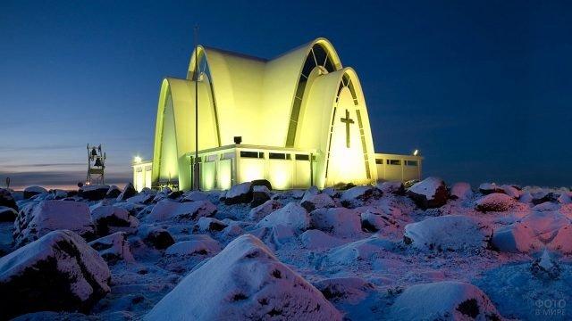 Церковь Коупавогюр в ярком освещении на фоне необычного ландшафта