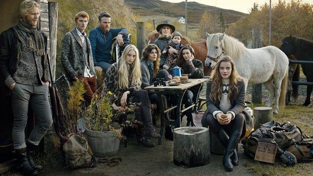 Фермерская семья сидит у стола, рядом с лошадьми