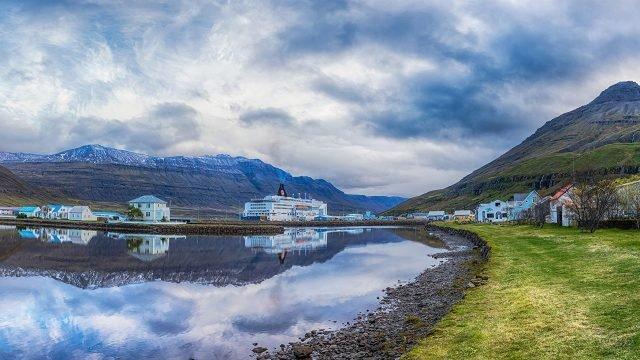 Голубое небо с облаками и домами отражаются в речке, текущей рядом