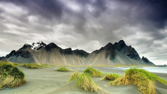 Громоздкие серые тучи над горами у моря