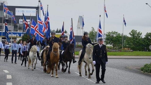 Конные люди с флагами Исландии на дне независимости