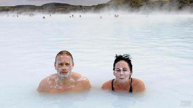 Люди купаются в горячих источниках с обмазанными лицами
