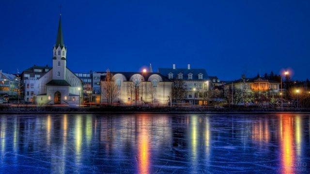Расплывчатое отражение огней города Рейкьявик на льду