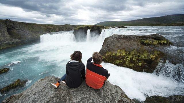 Туристы сидят на скалистом обрыве и смотрят на водопад