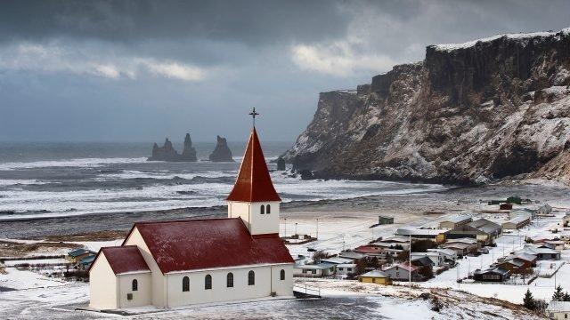 Заснеженная церковь рядом с маленьким городом у гор