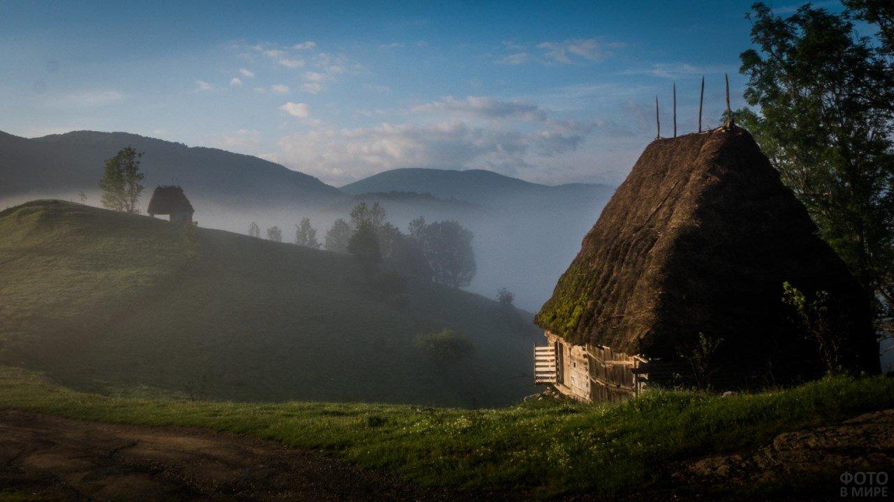 Дом с соломенной крышей на фоне туманного холма