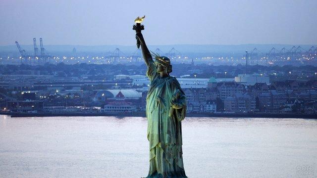 Горящий факел в руках Статуи Свободы на фоне вечернего Нью-Йорка