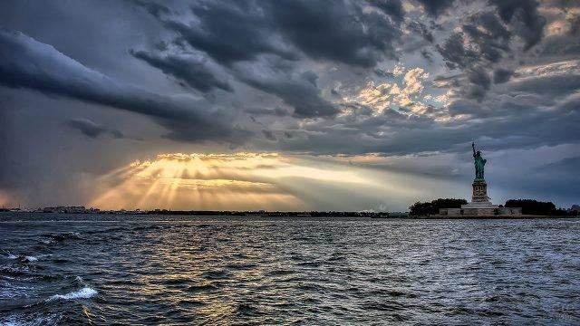 Лучи солнца пробиваются из-за туч над заливом и Статуей Свободы в Нью-Йорке