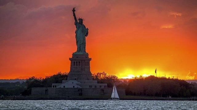 Парусник у подножья Статуи Свободы на фоне оранжевого заката