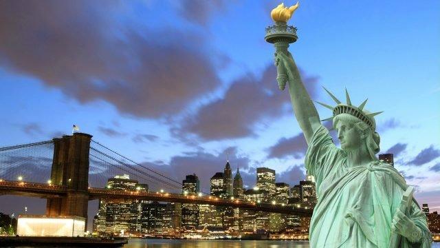 Статуя Свобды на фоне вечерних огней Нью-Йорка