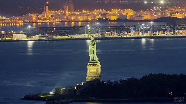 Статуя Свободы на фоне вечерних огней порта в бухте Нью-Йорка