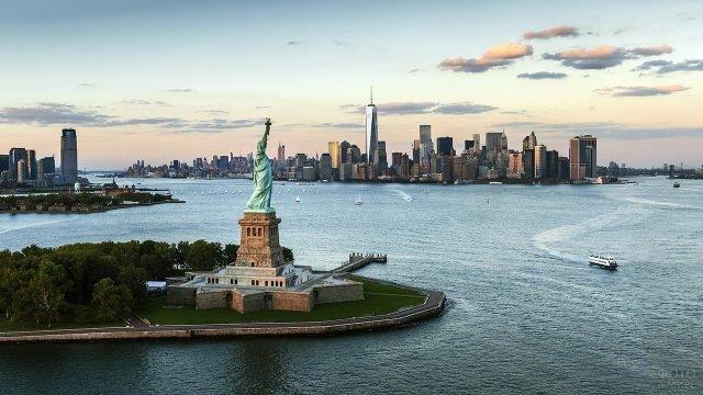 Статуя Свободы на одноимённом острове на фоне вечернего Нью-Йорка