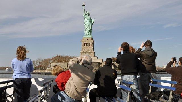 Туристы фотографируют Статую Свободы с верхней палубы прогулочного кораблика