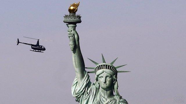 Вертолёт пролетает над Статуей Свободы