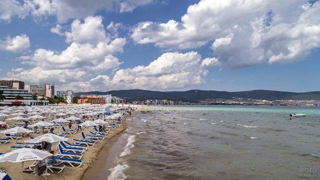 Шезлонги под зонтиками на пляже курорта Солнечный берег
