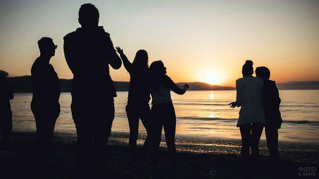 Силуэты туристов на рассвете у побережья курорта Солнечный берег