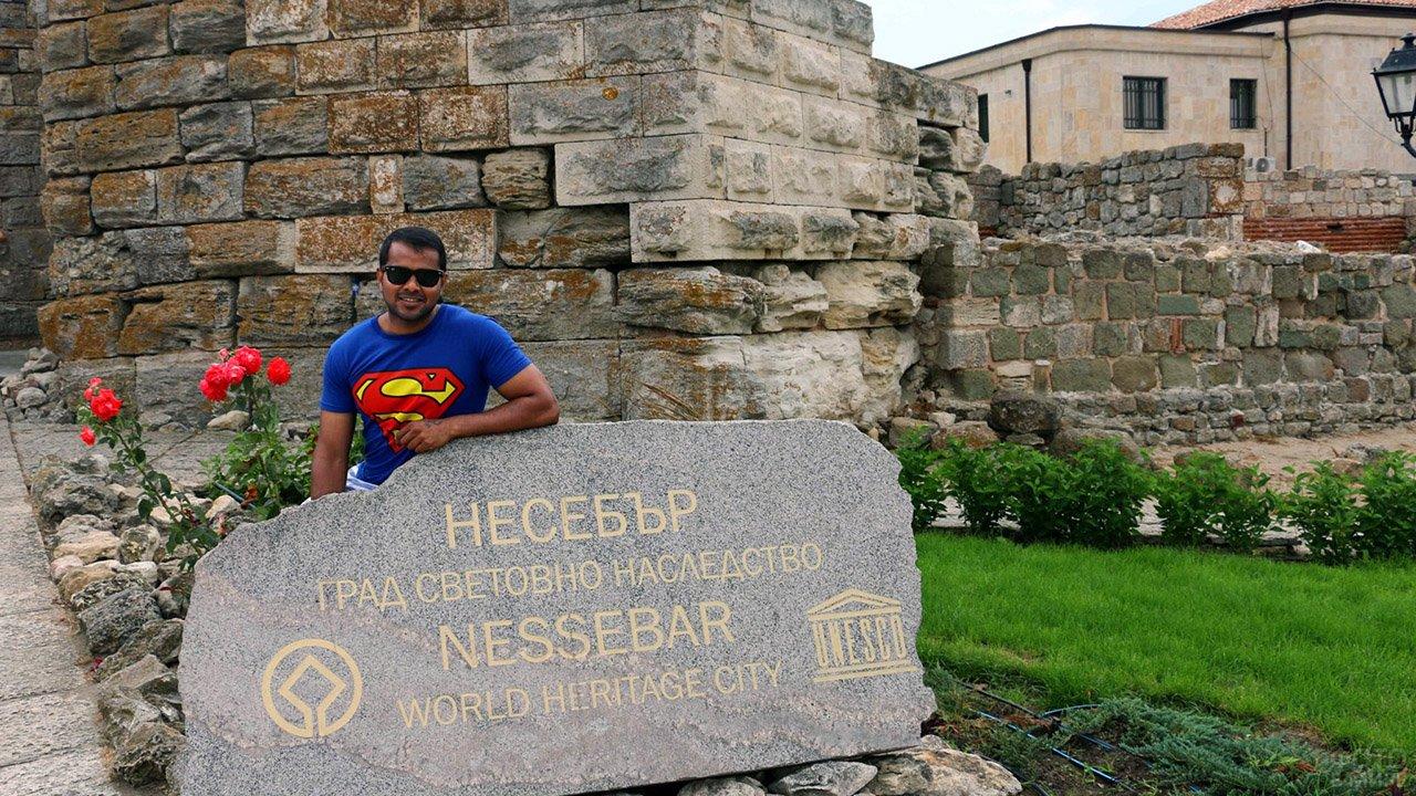 Турист у памятного знака античного города Несебр в курорте Солнечный берег