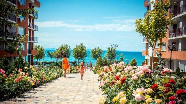 Туристка с маленькой дочкой идёт через розарий к пляжу на курорте Солнечный берег