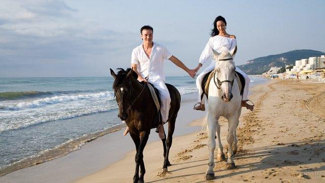 Влюблённая парочка на конной прогулке по побережью курорта в Болгарии