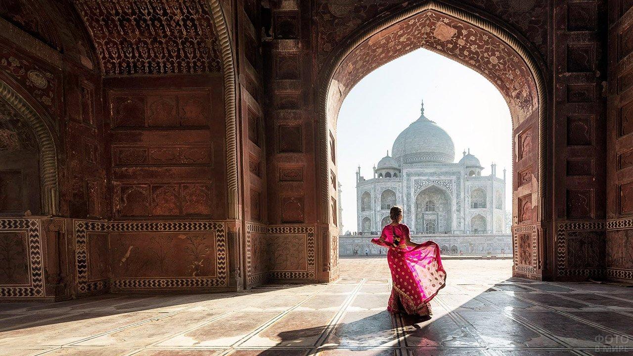 Девушка в индийском наряде под аркой ворот на фоне Тадж-Махала