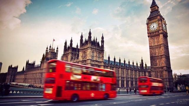 Туристические автобусы мчатся по Вестминстерскому мосту к башне Биг-Бен