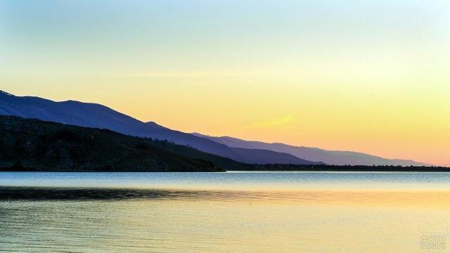 Сиреневые силуэты гор на берегах Байкала в лучах заката